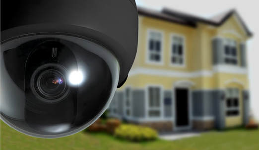 home surveillance camera showing black mini dome CCTV camera and house to background